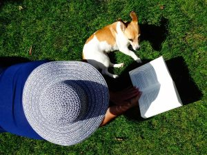 Pet care advice - Lady in a hat reasding a book with a dog sitting next to her